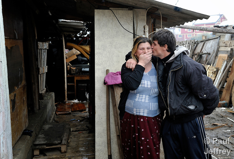 Giltena Duda gets a kiss from her husband Ismet Sabanaj outside their home in the Zemun Polje Roma neighborhood of Belgrade, Serbia. Ms. Duda is pregnant with her seventh child. They are Roma refugees from Kosovo, and thus legally marginalized in Serbia. They built their home on unregistered land and pirate their electrical hookup. Without legal residency, their children can't attend a regular school, and they have difficulties getting formal employment. Yet both participate in an adult literacy program sponsored by the Branko Pesic School, where their children attend classes. The school is supported by Church World Service.