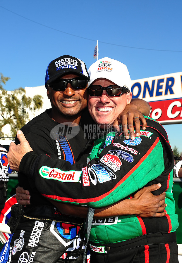 Feb. 9, 2012; Pomona, CA, USA; NHRA funny car driver John Force (right) and top fuel dragster driver Antron Brown during qualifying at the Winternationals at Auto Club Raceway at Pomona. Mandatory Credit: Mark J. Rebilas-