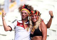 A Germany fan celebrates as he has his photograph taken with his girlfriend inside the Estadio Castelao ahead of kick off