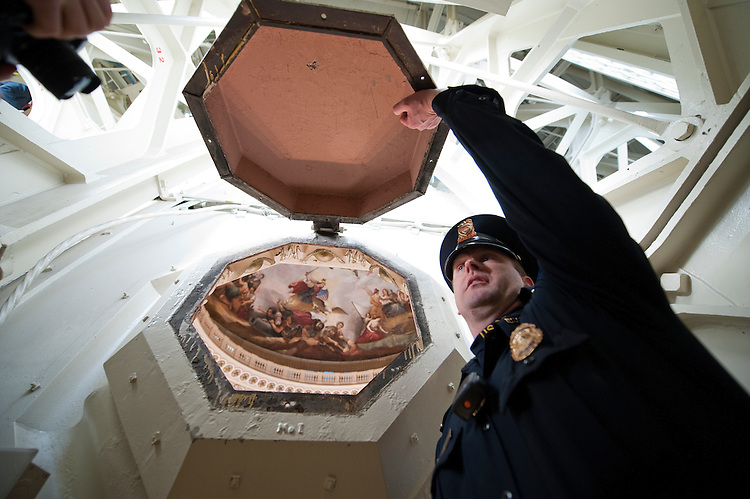 UNITED STATES - Dec 19: U.S. Capitol Police Officer Adam Taylor holds open one of the coffer windows in the ceiling of the U.S. Capitol dome during a media tour December 19, 2013 in Washington, DC. The dome of the U.S. Capitol will be undergoing a restoration project to halt deterioration in the dome's cast iron as well as ensuring the protection of the interior of the dome and rotunda. (Photo By Douglas Graham/CQ Roll Call)
