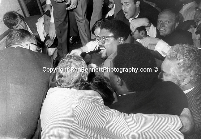 Rosey Grier and Robert Kennedy staff try to get the gun away from Sirhan Sirhan after the shooting at the Ambassador Hotel Angeles California,  Sirhan Sirhan held by RFK staff and Rosey Grier, Robert F. Kennedy, RFK, Bobby, Bobby Kennedy, assassination of RFK, assassination, assassination of Robert F. Kennedy, Ethel Kennedy, June 5 1968, Sirhan Sirhan,  Ambassador Hotel Los Angeles California, Rosey Grier, George Plimpton, Rafer Johnson, Photojournalism, Photojournalist, collecting, editing, presenting news photographs, Photojournalism provides visual support for stories mainly in the print media,  Commercial photography's main focus is to sell a product or service, Fine Art photography are photographs that are created to fulfill the creative vision of the photographer, Robert F. Kennedy assassination Ambassador Hotel Los Angeles CA Ron Bennett Photo's, RFK Photo's by Ron Bennett, Robert F. Kennedy photographs by Ron Bennett, Robert F.  Bobby Kennedy assassination photographs by Ron Bennett,