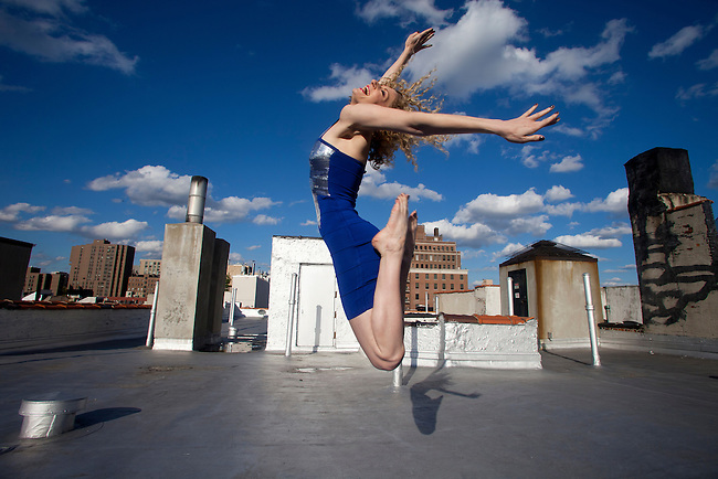 Woman in Blue on Roof top. Sexy 30's woman jumps for joy on an urban roof top.