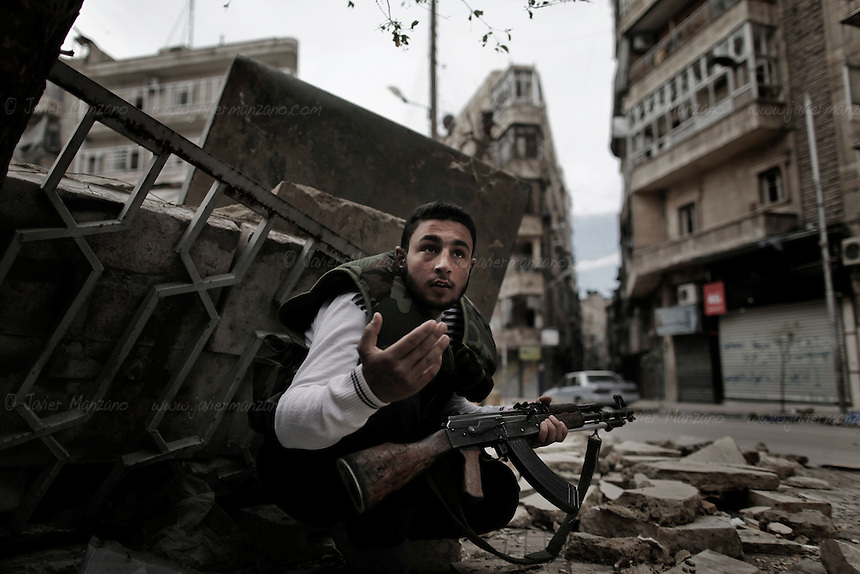 A Free Syria Army soldier motions to civilians to seek cover after a sniper (in an unknown position) opened fire at the Sha'ar neighborhood of central Aleppo. In the war for the city of Aleppo, snipers can hold a line of several streets and can take weeks to locate and neutralize them. Both sides (the Free Syria Army and the regime) rely heavily on snipers - the cat and mouse game of Aleppo's front lines...© Javier Manzano.............