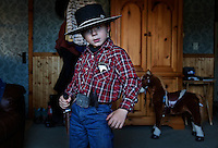 Dressed as a cowboy Sheriff, Tanner Lauman takes a stance to not be reckoned with.<br /> <br /> Kitty Lauman trains mustangs--as she says working with the horses, not against them.  They have a ranch in Prineville, OR.<br /> <br /> Kitty, her husband Rick and their children, Josie, 2 &frac12;,  and Tanner, 5,  ride mustangs. Kitty Lauman started her career as a horse trainer at the tender age of nine, under the guidance of her grandfather, John Sharp. <br /> <br /> She later became a top Pee Wee and High School Rodeo contestant, competing in barrel racing and cutting, among other events. Despite her mother's assertion that &quot;horse training isn't a real job,&quot; Kitty managed to make a living as a trainer after high school (and her mom now helps out with the business!) <br /> <br /> Kitty won the title of Miss Rodeo Oregon in 1994, and since then, has continued to expand her horse training knowledge and experience.  She placed second in the Extreme Mustang Makeover, a national competition in 2008.