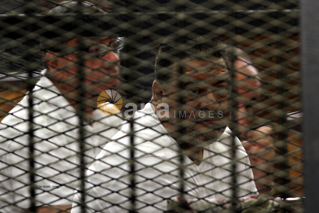 Egyptian Muslim Brotherhood members stand inside the defendants cage during their trial in the capital Cairo on June 17, 2014. The court postponed  to July 23 the verdict in the trial of Muslim Brotherhood Supreme Guide Mohamed Badie and 50 others in the case of the Rabaa operating room. Photo by Mohammed Bendari