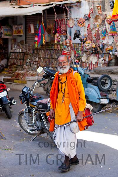 Hindu sadhu holy man wearing traditional robes walks in old town in Udaipur, Rajasthan, Western India
