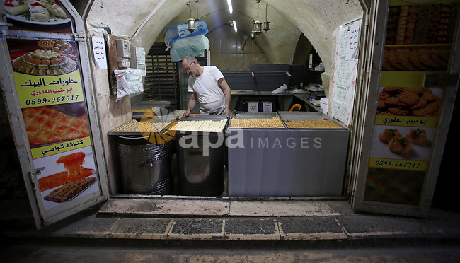 A Palestinian vendor sells traditional pancakes known as ''Qatayef'' on the Muslim holy fasting month of Ramadan at his shop in the Old City of the West Bank town of Nablus on May 28, 2017. Ramadan is sacred to Muslims because it is during that month that tradition says the Koran was revealed to the Prophet Mohammed. The fast is one of the five main religious obligations under Islam. More than 1.5 billion Muslims around the world will mark the month, during which believers abstain from eating, drinking, smoking and having sex from dawn until sunset. Photo by Ayman Ameen