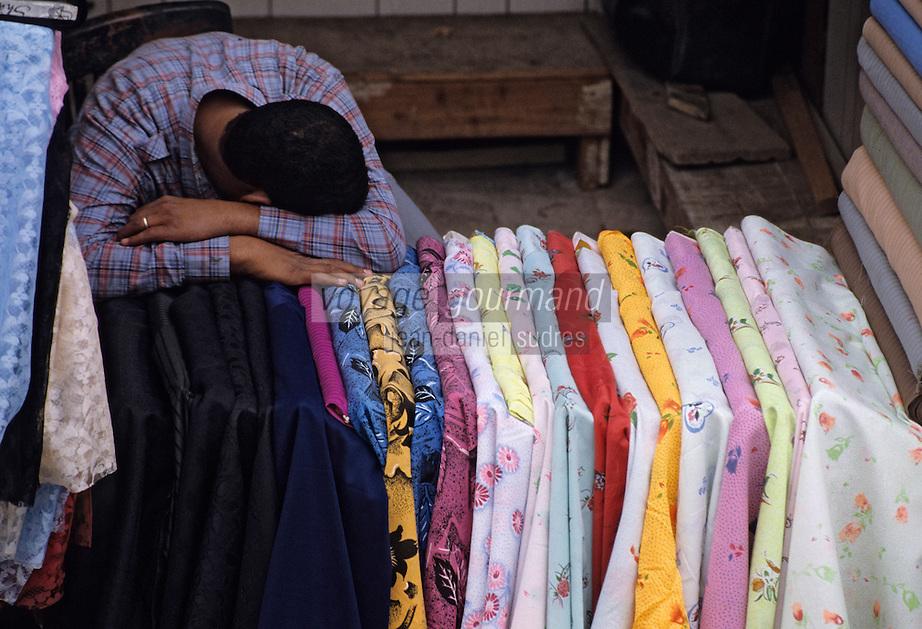 Afrique/Egypte/Le Caire: Marchand de tissus somnolent dans les souks de la rue des Mosquées