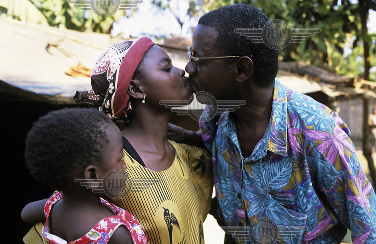 An HIV positive father kisses his wife goodbye as he leaves for work.