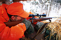 A deer hunter in orange safety hunting gear aims a rifle within a winter hunting blind.