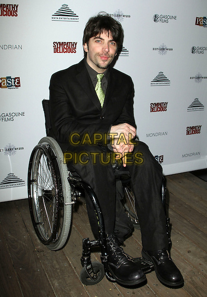 """CHRISTOPHER THORNTON.""""Sympathy for Delicious"""" Release Party held at the Mondrian Hotel's SkyBar,.West Hollywood, California,.27th April 2011..full length sitting in wheelchair disabled black suit green tie .CAP/ADM/KB.©Kevan Brooks/AdMedia/Capital Pictures."""