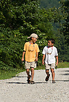 Nine- and seven-year-old brothers walk along a road to go fly fishing on the James River, Missouri.