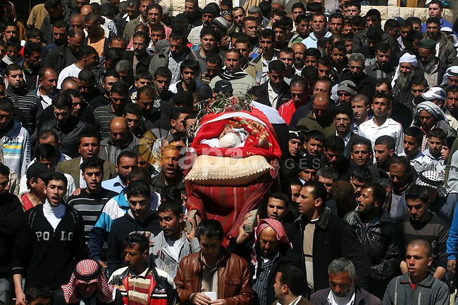 Palestinians carry the body of Zakariya Abu Eram during his funeral in the West Bank town of Yatta, near Hebron, Friday, March 9, 2012. According to the Israeli military, a Palestinian stabbed an Israeli soldier in the neck during a raid in the town of Yatta, seriously wounding him. The soldier opened fire, wounding the assailant and killing another man who was not involved in the attack, witnesses said. Photo  Issam Rimawi