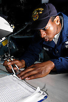 060410-N-7981E-188 Pacific Ocean (April 10, 2006)- Quartermaster Third Class Darnell Jeanmarie plots a course while standing watch on the bridge of the Arleigh Burke-class Guided Missile Destroyer USS Shoup (DDG-86). Shoup is currently underway in the Western Pacific area of operations. U.S. Navy photo by Photographer's Mate Airman James R. Evans (RELEASED)