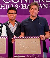 HAIKOU, CHINA - OCTOBER 28:  Hollywood actor Hugh Grant (R) of Great Britain poses with his handprints near Dr. Ken Chu (L), Vice Chairman of Mission Hills Group and during a press conference as part of the Mission Hills Star Trophy on October 28, 2010 in Haikou, China. The Mission Hills Star Trophy is Asia's leading leisure liflestyle event and features Hollywood celebrities and international golf stars.  Photo by Victor Fraile / studioEAST