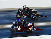 Nov. 10, 2012; Pomona, CA, USA: NHRA pro stock motorcycle rider James Underdahl (near lane) races alongside Matt Guidera during qualifying for the Auto Club Finals at at Auto Club Raceway at Pomona. Mandatory Credit: Mark J. Rebilas-