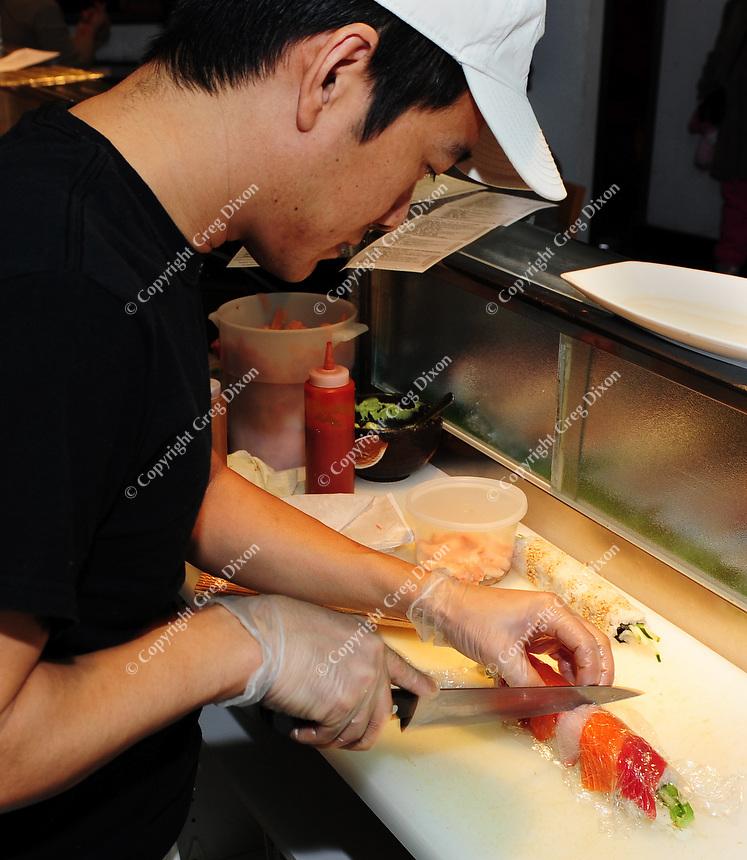 Urgen Dorjee prepares sushi behind the bar of Wasabi Japanese Restaurant on State Street
