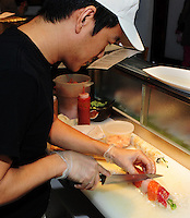 Urgen Dorjee prepares sushi behind the bar of Wasabi Japanese Restaurant on State Street