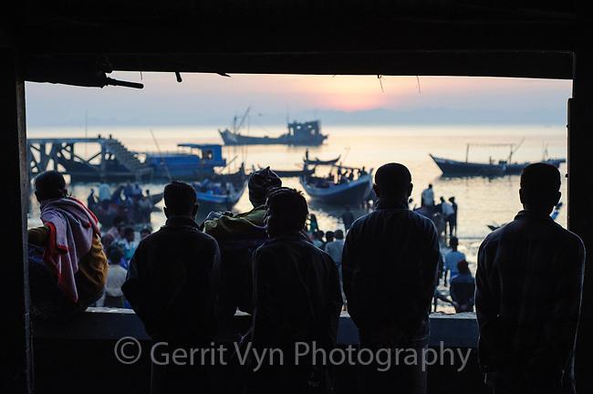 Fishermen overlooking the harbor at dawn. Sittwe, Rakhine State, Myanmar.