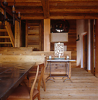 The all wood interior of the open-plan dining area of the chalet with a unique handmade lamp in the centre of the room
