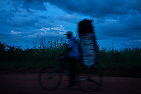 Man rides bycylce at dusk past a site of an Lord's Resistance Army (LRA) attack on a bus, during which 10 people were killed, Dure Village, Pader District. During LRA insurgency, movement outside camps for internally displaced persons (IDPs) was restricted, especially after dark and riding bycycles or motorcycles was forbidden by the LRA. LRA claimed people use them to inform Ugandan army of LRA's movements, so anyone caught riding a bycycle could be beaten, maimed or killed.