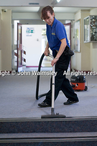 Cleaner vacuuming the corridors,  State Secondary Roman Catholic school.