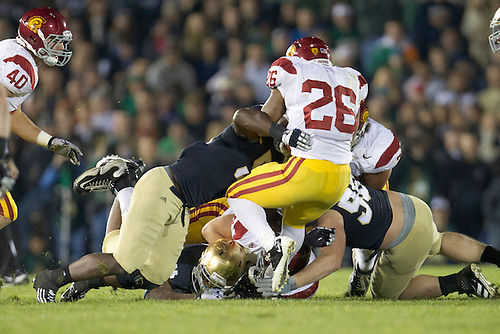 USC running back Marc Tyler (#26) is tackled by Notre Dame defenders during second quarter of NCAA football game between Notre Dame and USC.  The USC Trojans defeated the Notre Dame Fighting Irish 31-17 in game at Notre Dame Stadium in South Bend, Indiana.