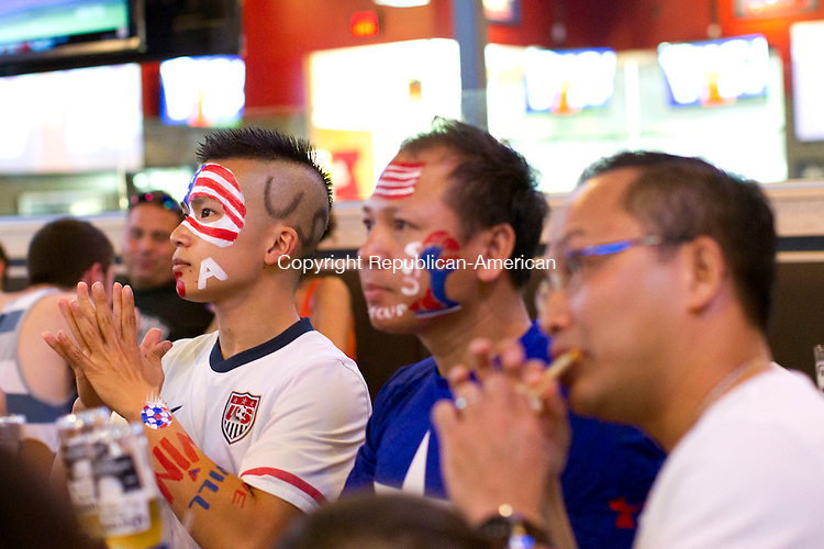 Waterbury, CT- 01 July 2014-070114CM04-  Vinh Nguyen,  left, his uncle Don Phan of Bristol watch the U.S Mens soccer match against Belgium during World Cup action at Buffalo Wild Wings in Waterbury on Tuesday.    Christopher Massa Republican-American