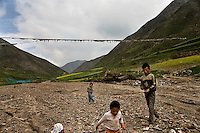 Children play in a dried up drainage bed between mountiains above Xiahe, Gansu, China.  Xiahe, home of the Labrang Monastery, is an important site for Tibetan Buddhists.  The population of the town is divided between ethnic Tibetans, Muslims, and Han Chinese.