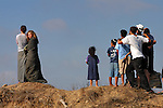 Standing on a hill in the Israeli settlement of Kefar Darom, Gaza Strip, kids watch a shooting incident between Israeli army and Palestinian militants taking place at the neighboring Palestinian refugee camp of Dir El-Balach.