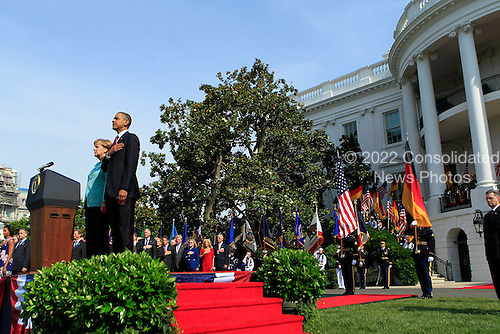 United States President Barack Obama, right, puts his hand over his heart during the playing of the national anthem at a welcoming ceremony for  Angela Merkel, Germany's chancellor, on the South Lawn of the White House in Washington, D.C., U.S., on Tuesday, June 7, 2011. .Credit: Andrew Harrer / Pool via CNP