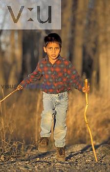Romanian boy hiking on trail with walking sticks, Montana, USA