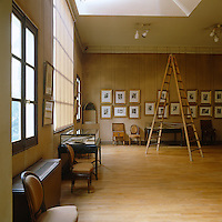 Sketchbooks and other memorabilia are displayed in glass cabinets and framed paintings line the walls of the principal working space of the Musee Delacroix