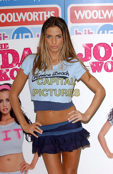 """JORDAN - KATIE PRICE .Signs copies of her new dvd """"The Jordan Workout"""" At  Woolworths, Lakeside Shopping Centre, West Thurrock, Essex, UK.January 5th, 2006.Ref: BEL.full length hands on hips blue shirt ruffle mini skirt.www.capitalpictures.com.sales@capitalpictures.com.© Capital Pictures."""