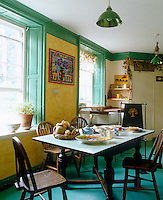 Green painted floors and woodwork create a cheerful contrast to the canary-yellow walls of this country kitchen