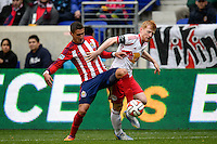 Leandro Barrera (11) of Chivas USA and Richard Eckersley (2) of the New York Red Bulls. The New York Red Bulls and Chivas USA played to a 1-1 tie during a Major League Soccer (MLS) match at Red Bull Arena in Harrison, NJ, on March 30, 2014.