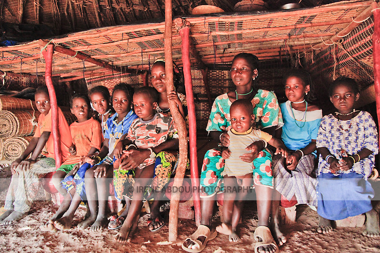In the Fulani village of Jolooga in northern Burkina Faso, a family sits on a traditional bed in a house made of handwoven straw mats supported by thin sticks of wood.  Additional straw mats serve as a mattress.