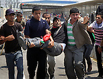 """Palestinians carry a wounded protester after Israeli troops opened fire during a massive march heading towards the Erez border crossing in the northern Gaza Strip, on May 15, 2011, as people gathered to mark the """"nakbah"""" or """"catastrophe"""" anniversary of Israel's creation in 1948, as a result of which more than 760,000 Palestinians -- estimated today to number 4.7 million with their descendants -- were pushed into exile or driven out of their homes. According to medics 45 people were injured when the Israeli troops opened fire. Photo by Ali Jadallah"""