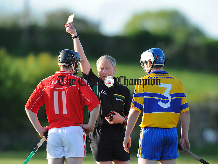 Referee Ger Hoey issues a yellow card to Crusheen's  Joe Meaney and Sixmilebridge's Aidan Quilligan during their Clare Champion Cup game at Crusheen. Photograph by John Kelly.