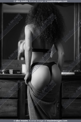 Sensual black and white portrait of back of a sexy woman wearing lingerie dressing up in front of a mirror