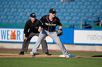 Charlotte Knights first baseman Zack Collins (8) holds Brandon Nimmo (not shown) on as umpire Brian Peterson looks on during an International League game against the Syracuse Mets on June 11, 2019 at NBT Bank Stadium in Syracuse, New York.  Syracuse defeated Charlotte 15-8.  (Mike Janes/Four Seam Images)