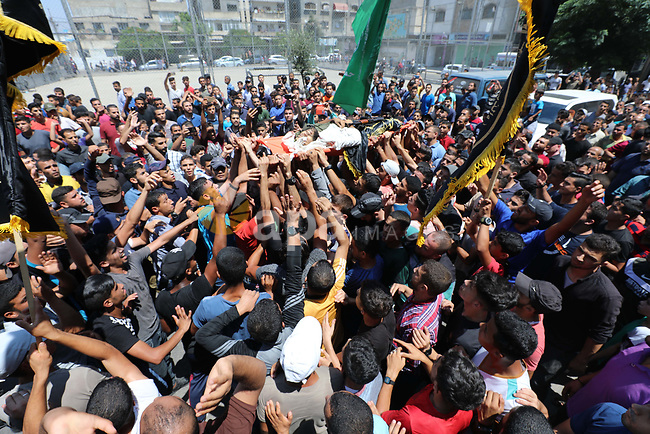 Mourners carry the body of Palestinian Mahmoud Al-walayda, one of three armed Palestinians killed overnight in Israeli fire along the border with the Gaza Strip, during his funeral in Beit Lahya in northern Gaza strip on August 18, 2019. Israeli forces last night killed three Palestinians and injured a fourth one in an artillery attack near the town of Beit Lahia, north of the Gaza Strip, according to the Ministry of Health. Photo by Ramadan al-Agha