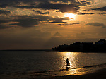 A young lady's dress blows in the sea breeze as she wades through the shallow waters of Shell Point Beach at sunset.