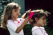 MR / Schenectady NY. Girl (7) brushes her sister's (5) hair. Book original from Brothers and Sisters. MR: Cam1, Cam3. © Ellen B. Senisi