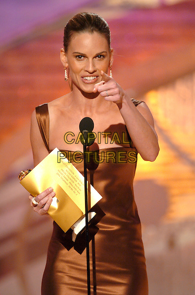 HILARY SWANK.62nd Annual Golden Globe Awards, Beverly Hills, Los Angeles, California.January 16th, 2005.half length, microphone, stage, pointing, gesture, brown silk satin dress.www.capitalpictures.com.sales@capitalpictures.com.Supplied by Capital Pictures.