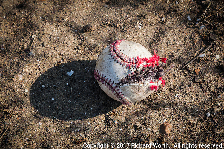 Split open and useless, a discarded baseball lies on the ground casting its lonely shadow.