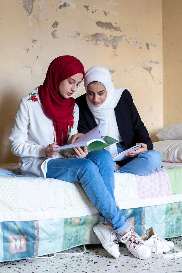 Syrian Refugee sisters study together in their shared bedroom in Lebanon.