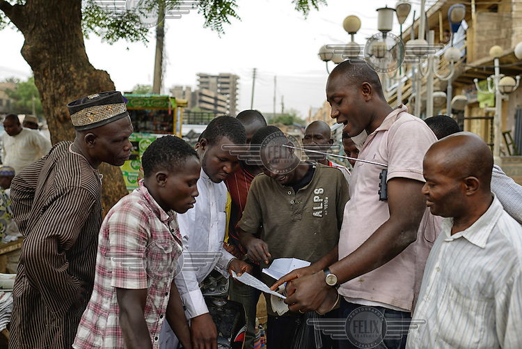 A group of men gather around a man with a radio to hear the latest results from the 2015 Presidential elections. Initial results indicated a tight race but as the counting of votes progressed it soon became clear that Muhammadu Buhari, leader of the APC (All Progressives Congress Party), had prevailed.
