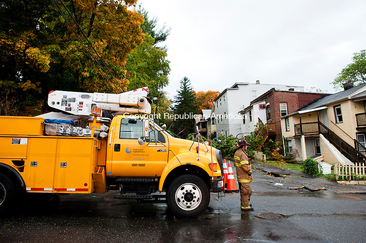 WATERBURY, CT - 7 October 2013-100713EC29--   A firefigher keeps watch at the intersection of Green and John Streets in Waterbury's Brooklyn neighborhood Monday. Neighbors say lightning hit a tree shortly before a large branch fell on a house. Erin Covey Republican American.
