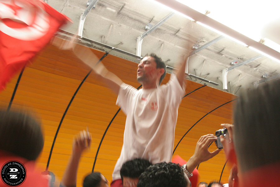 A Tunisian National Soccer Team fan leads the cheers while hoisted on top of the shoulders of another Tunisian fan at the Marienplatz City Ceter subway station in Munich, Germany on Wednesday, June 14th, 2006. The fans were on their way to the Bayern-Munich arena  to watch Tunisia play their FIFA World Cup first round match against Saudi Arabia .  The two teams tied at 2-2.